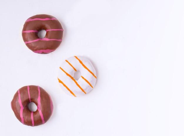Три пончики в шоколадной и ванильной глазури на белом фоне с местом для текста