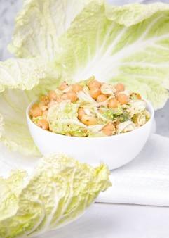 Вегетарианский салат в белой маске с нутом и капустой на светлом фоне