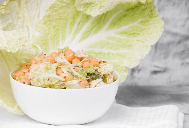 Вегетарианский салат в белой маске с нутом и капустой на светлом бетонном фоне