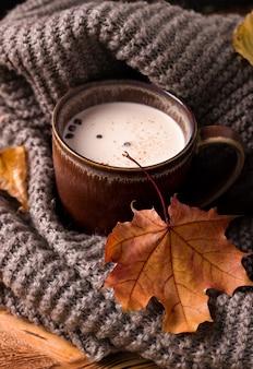 灰色のスカーフの横にある牛乳と秋の飲み物