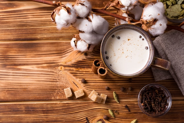 マサラティーは、スパイスと綿の横にある木製のテーブルに牛乳を入れた伝統的なインドの飲み物です。