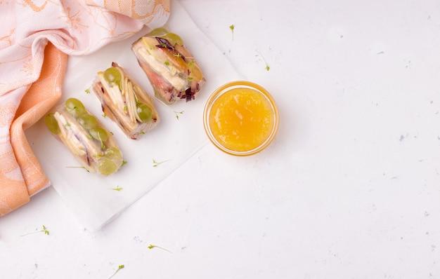 Блинчики с начинкой из фруктов на рисовой бумаге на белом, рядом с апельсиновым джемом.