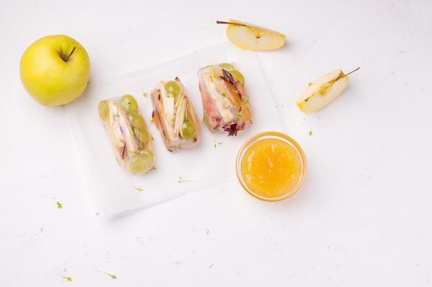 Сладкие блинчики с начинкой из фруктов рядом со свежим яблоком на белом. есть место для текста