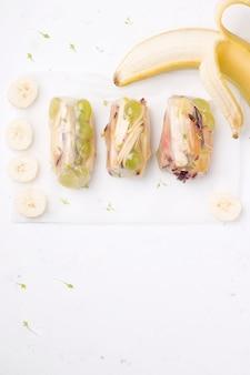 Сладостные блинчики с начинкой плодоовощ рядом с свежей, банан на белизне. есть место для копирования. вегетарианское блюдо