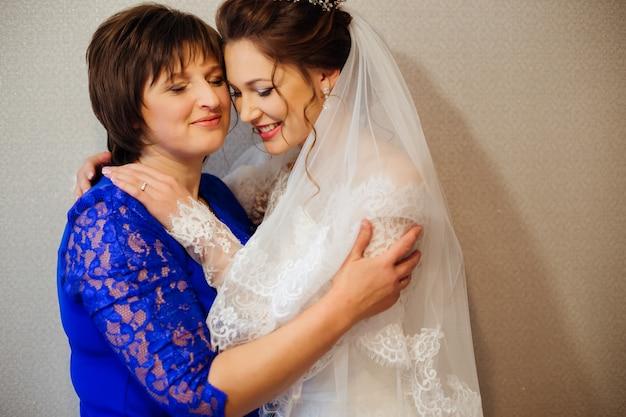 結婚式の前に母と娘が優しく抱き締めて目を閉じた