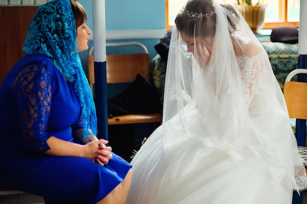 豪華な白いドレスを着た花嫁は結婚式の前に泣き、母親は彼女を落ち着かせる