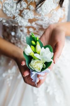 白いバラとブートニアのクローズアップ。ウェディングドレスの花嫁