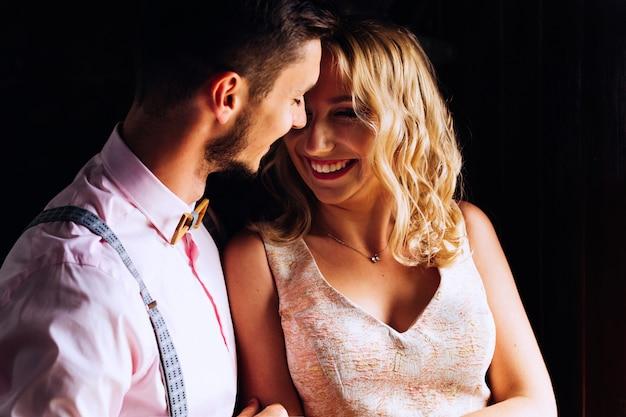 Парень нежно обнимает свою девушку, которая искренне смеется на темном фоне