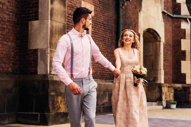 Парень в красивой одежде держит свою любимую девушку на пробежке