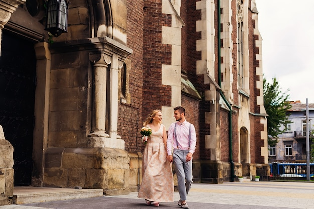 Девушка в длинном платье держит букет и ее парня рядом с ней, и они вместе гуляют у входа в красивое кирпичное здание