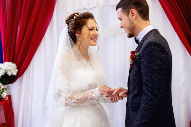 幸せなカップルは結婚指輪を交換し、お互いを見ました