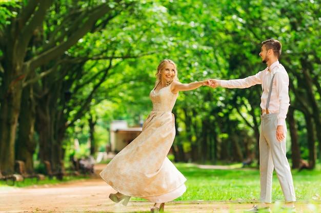 Пара стильной одежды танцует в парке на фоне деревьев