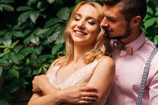 かわいい女の子が目を閉じ、彼女のボーイフレンドが背景の緑の葉に彼女の近くに立っています。