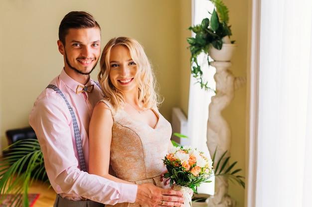 Жених обнимает свою невесту, которая держит свадебный букет в комнате с украшениями