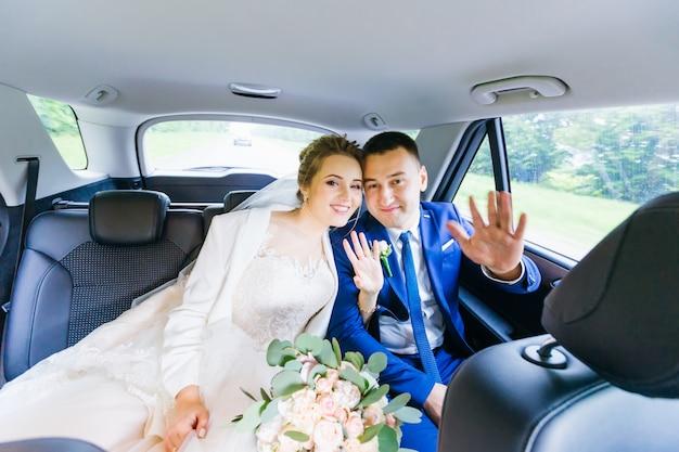 新婚夫婦はカメラを見て車に座っています。