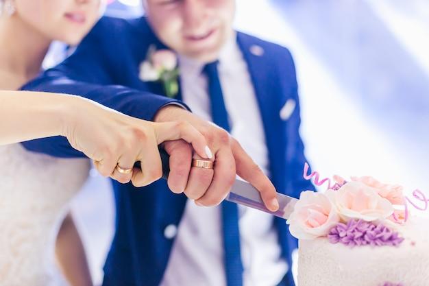 新婚夫婦はナイフを持って一緒にケーキを切りました。