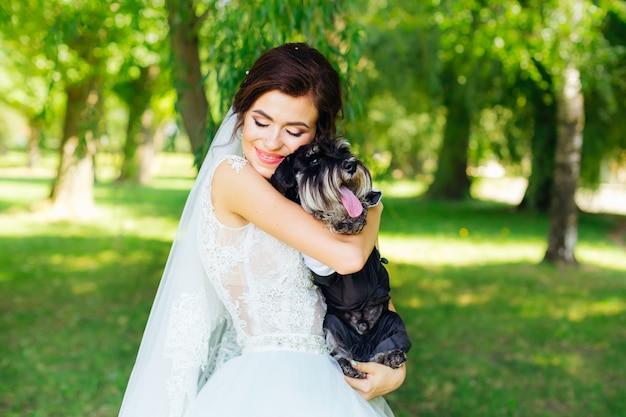 ウェディングドレスの美しい花嫁の手にミニシュナウザー