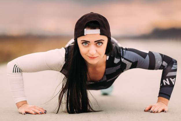 アスファルトの上に腕立て伏せを行うスポーツウェアの若い女性アスリート
