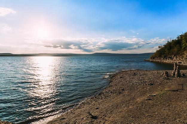 幻想的な夕日の湖の海岸線。日光で満たされた湾の空の海岸の風景