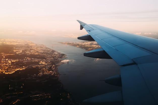 Вид крыла самолета с сиденья у окна над мостом васко де гама