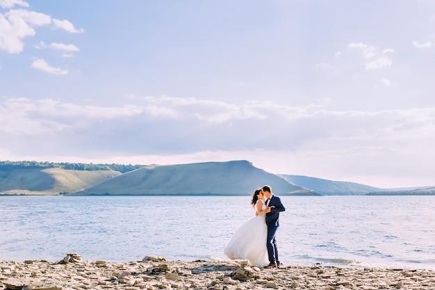 湖で新婚旅行を楽しんでいる素敵なカップル