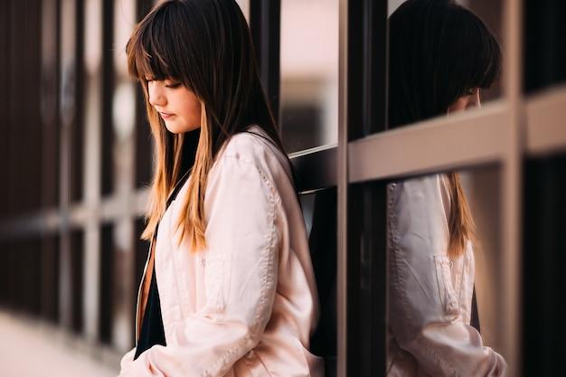Одинокий ребенок, сидящий на улице, печально опустил глаза