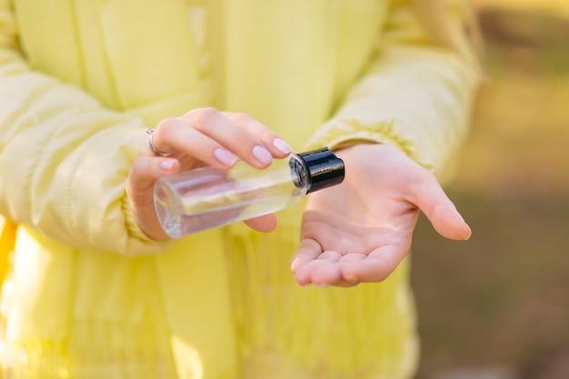 Женщина в жёлтой куртке лечит руки антисептическим спреем