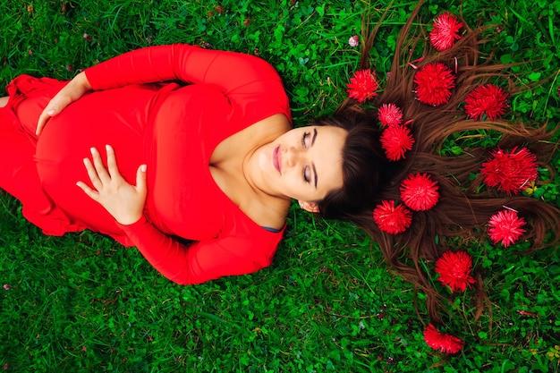 草の上に横たわって彼女の目を閉じて美しいドレスを着た妊娠中の女性
