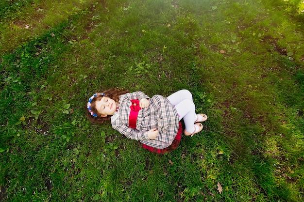 Маленькая красивая женщина лежит на зеленой траве и закрыла глаза