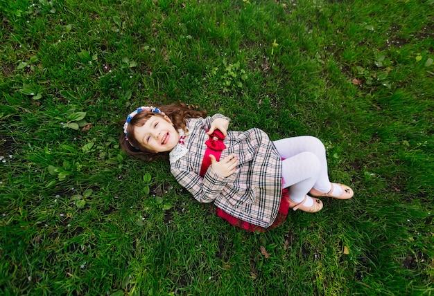 Женщина в красивом платье лежит на газоне и искренне улыбается