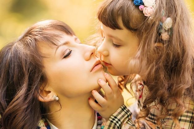 小さな娘がお母さんにキスをしたいと優しく触れた