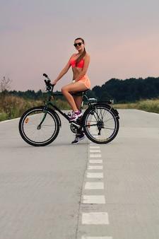 Симпатичный подросток в солнцезащитных очках и насыщенной оранжевой спортивной одежде катается на велосипеде на закате