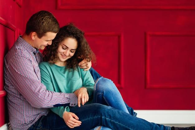 Чувственные объятия пары, сидящей на полу возле красной стены