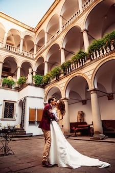 Поцелуй молодой пары во дворе с исторической архитектурой