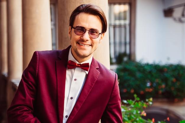 メガネとジャケットの若い男の笑みを浮かべてください。