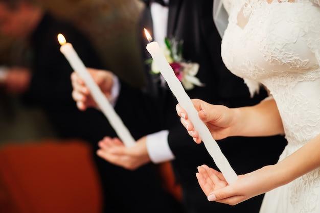 新婚夫婦は教会で手にキャンドルを持っています
