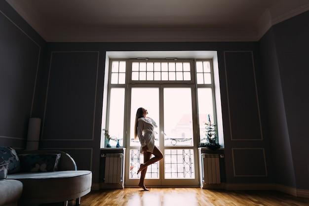 朝の窓の近くの完全な成長の少女のシルエット