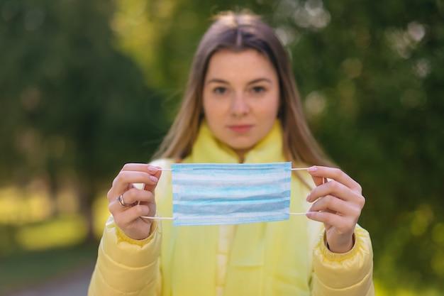 Женщина надевает медицинскую одноразовую маску, чтобы избежать заразных вирусов.
