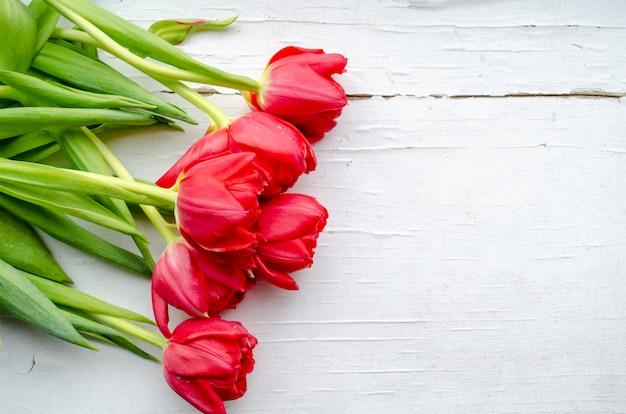 白い木製の背景に横たわる赤いチューリップの花束