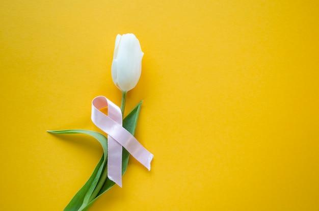 白いチューリップと黄色の背景にピンクのリボン