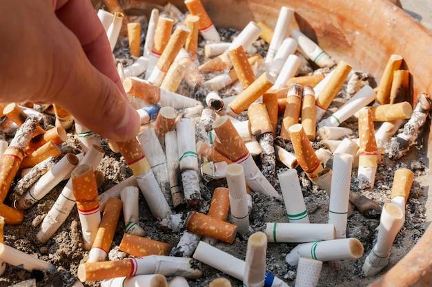今日の喫煙をやめ、手持ちのタバコの吸い殻を背景の多くのタバコの吸い殻に入れます