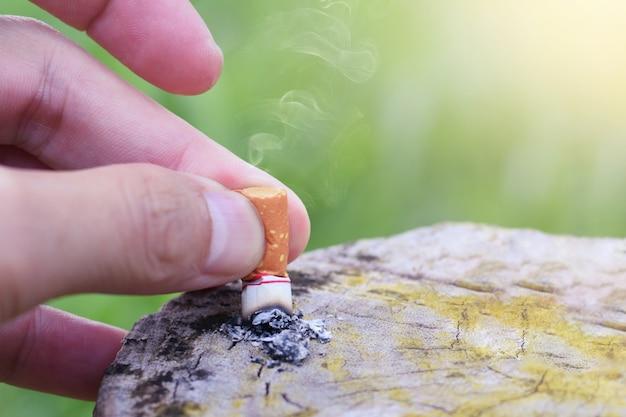 喫煙をやめる喫煙をやめる概念、手で落としたタバコが喫煙をやめるために木製のテーブルに降りてきた。