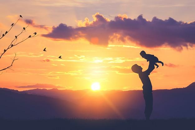 父と息子の赤ちゃんのシルエットが夕日の山々で遊ぶ