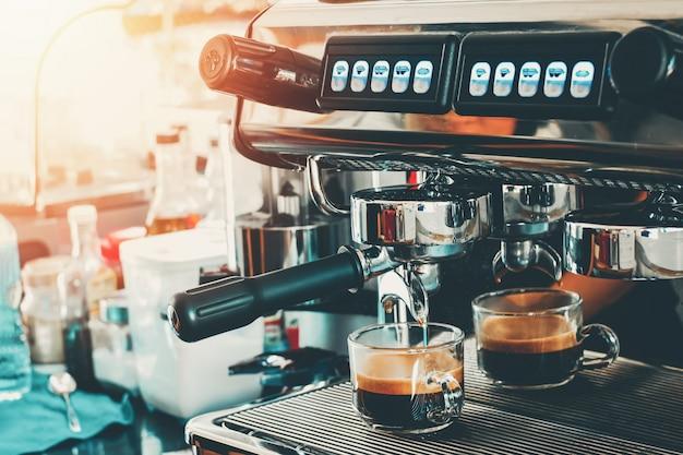 使用コーヒーメニューのためのガラスにコーヒーを注ぐコーヒーマシン