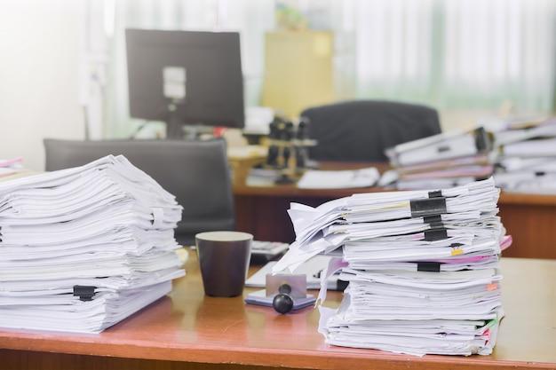 事務机上の書類積み重ね書類の山積み、事業書類請求及び現在の概要結果年次報告書を報告するための検討
