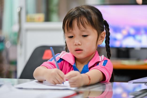 深刻な顔と不幸で自宅で宿題を作る幼児少女