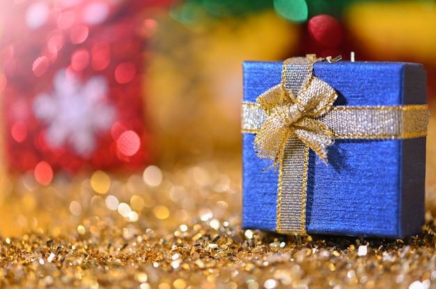 クローズアップゴールドグリスター背景に小さなギフトボックスクリスマスライト