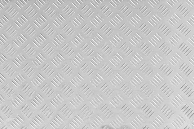 ステンレス製の床板、大まかなモチーフの金属シートの質感。剥ぎ取られた正方形のパターン