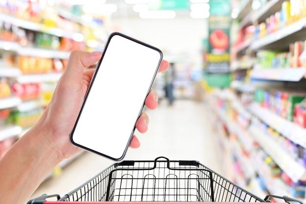 スーパーで買い物カゴを持つ空の白い画面のスマートフォンを持っている男の手