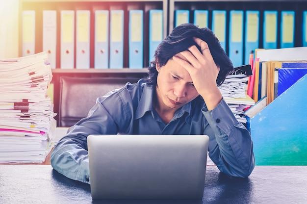 Азиатский деловой человек стресс или напряжение в офисе с синдромом выгорания на столе